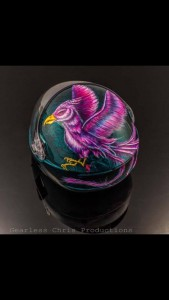 """Teal and Pink Phoenix"" (KISS Helmet, Owner: Sarah Hernandez, 2015) ""This helmet was one of the first truly intricate and challenging pieces I have created,"" Marissa says. ""I did a three step process with a teal marble-effect on the helmet. Then the phoenix is all painted by hand with acrylics. It took me about 50 hours to complete, but Sarah and I were both incredibly happy with the end result."""